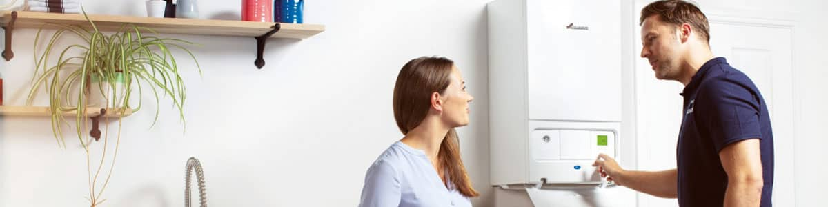 Woman having new boiler installed in kitchen by plumber